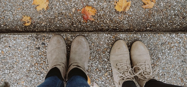 two pairs of shoes on the sidewalk with fall colored leaves on the ground.