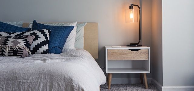 a brightly lit lamp on a bed side table