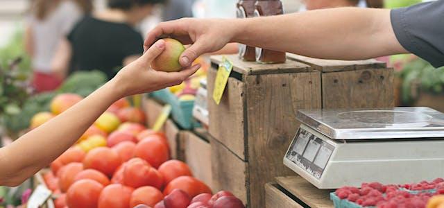 person handing apple to buyer