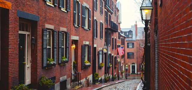 a sidewalk down a quiet boston street with brownstones on either side.