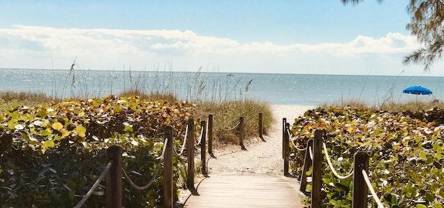 sandy entryway to a crystal clear beach on the ocean.