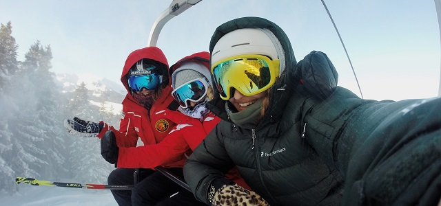 three skiers taking a selfie on a lift.