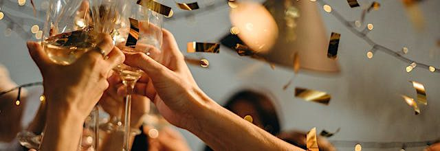 a group of people cheering to the new year with champagne glasses