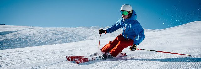 a skier gliding down a ski slope with blue skies and a blue jacket.