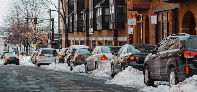 A line of cars parked on the side of the road in boston with a snow covered ground.