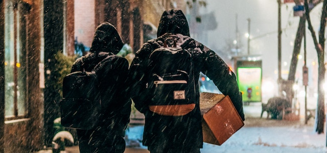 Two people carrying boxes down a snowy street in preparation for an apartment move.