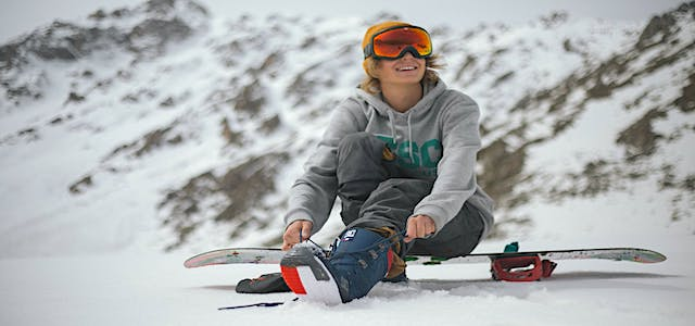 a girl on a snowboard enjoying a day at the slopes