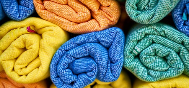 yellow, orange, blue, and green moving towels rolled up and ready for packing.