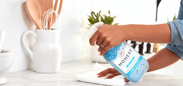 woman cleaning her counters with all purpose spray