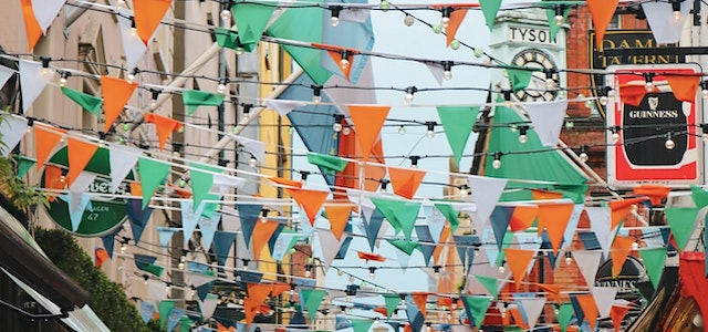 irish colored flags hanging from the buildings above a street